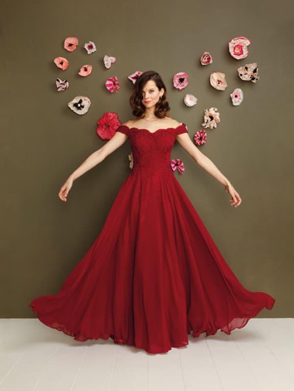 junge frau in weitem roten kleid vor einer dekorierten wand