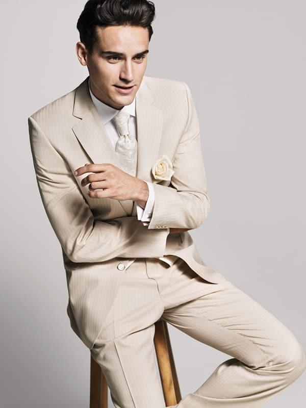 junger braeutigam in hellem anzug auf einem hocker