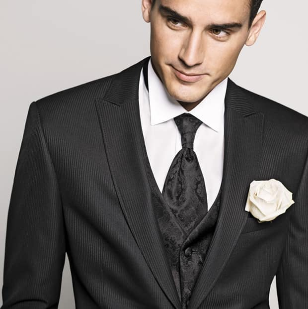 junger braeutigam mit krawatte und weisser blume im anzug