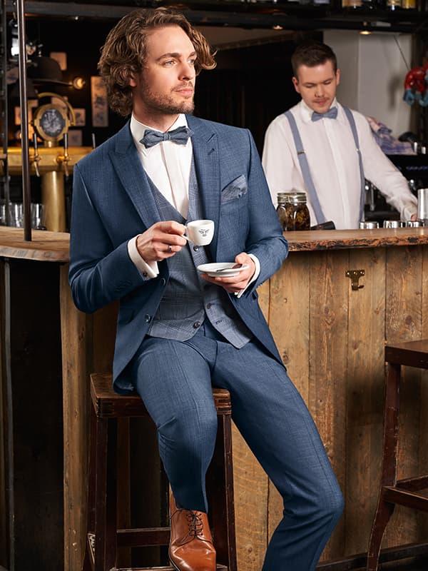 junger mann in blauem anzug sitzt auf einem barhovker und trinkt einen kaffe