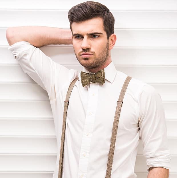 junger mann in weissem hemd fliege und hosentraegern